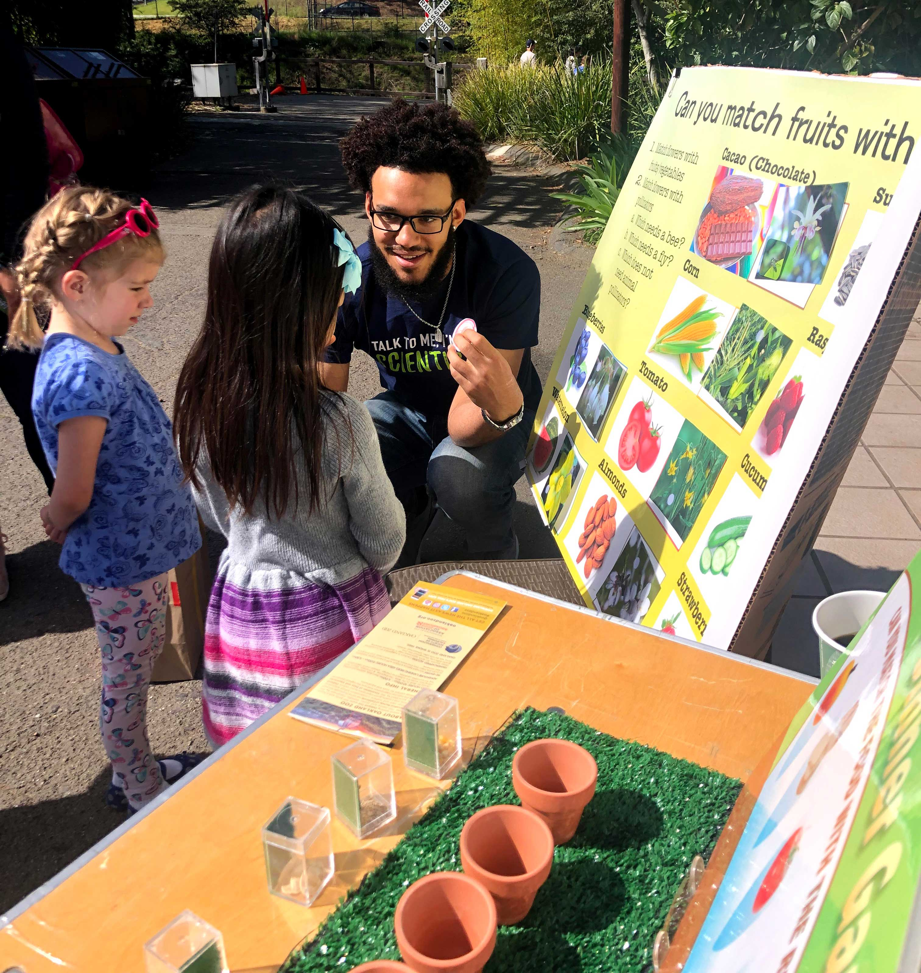 A man teaching young children about fruits in an outdoor setting