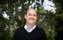 Headshot of dean David Ackerly standing in front of a tree