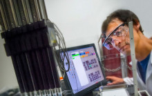 Researcher Adam Deutschbauer looks at a computer screen in a lab