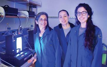 Sabeeha Merchant and other lab members standing in a lab next to a bioreactor.