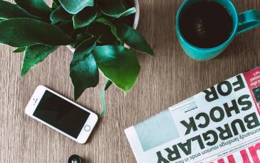 Overhead shot of phone, newspaper, tea in mug, and plant on table