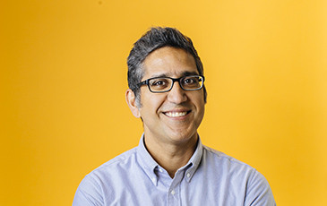 Arash Komeili smiling in front of a yellow background.